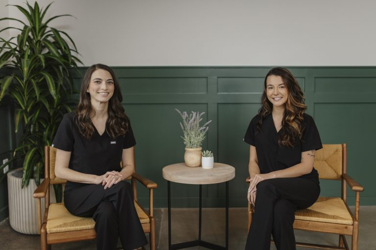 Dr. Diana D'aoust and staff member sit in the lobby of Nations Dental Studio