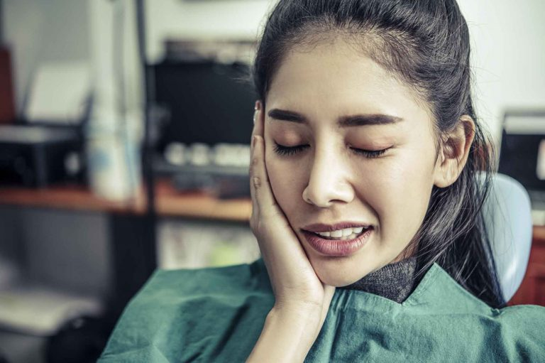 woman with tooth pain holding her cheek